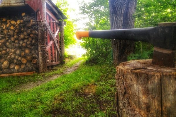 An axe in the foreground and a cord of wood in the background at Northern Sun Farm ecovillage.