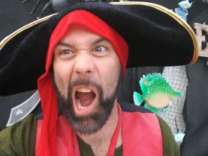A man in a pirate costume making a funny face.